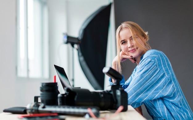Боком фотограф женщина смотрит на свои камеры Бесплатные Фотографии