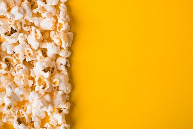 Плоский лежал попкорн на желтом фоне с копией пространства Бесплатные Фотографии