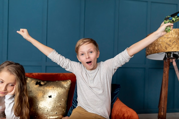 彼の妹とビデオゲームをプレイで勝つフロントビュー少年 無料写真