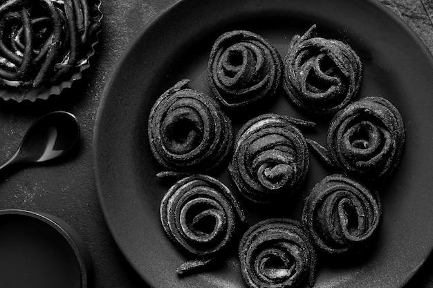 Плоская раскладка черной вкусной еды на темной тарелке и столе ...
