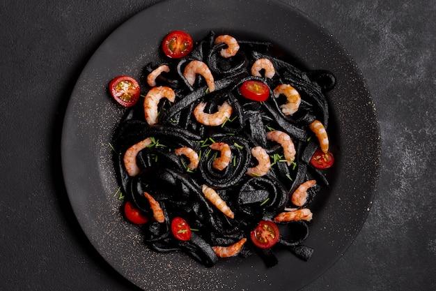Вид сверху черная паста с креветками на тарелке Бесплатные Фотографии