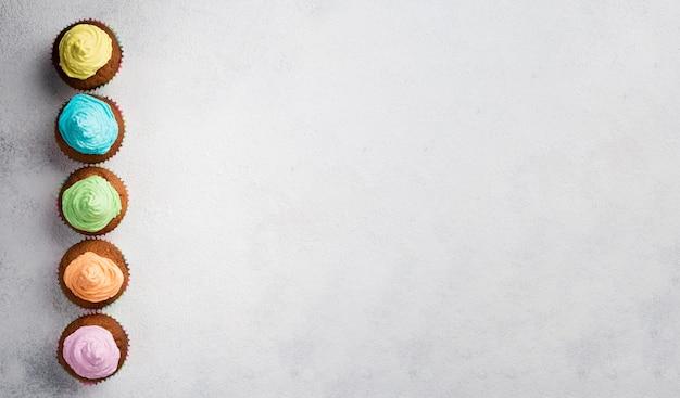 カラフルな艶をかけられたマフィンとコピースペースのトップビューフレーム 無料写真