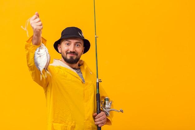 キャッチと釣り竿を持って誇りに思っている漁師 無料写真