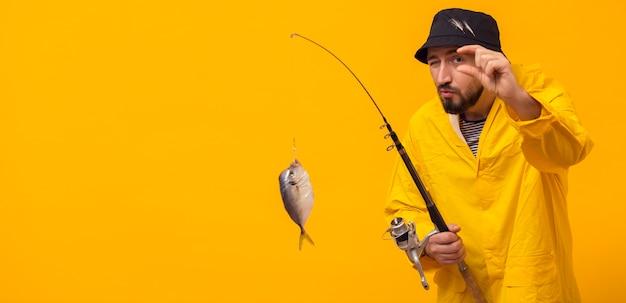 キャッチとコピースペースで釣り竿を保持している漁師の正面図 無料写真