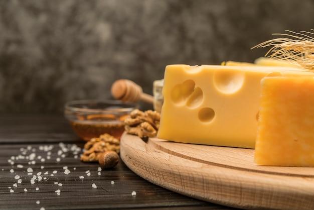 Крупным планом вкусный швейцарский сыр на столе с медом Бесплатные Фотографии