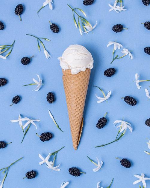 ブラックベリーと花に囲まれた白いバニラアイスクリーム 無料写真