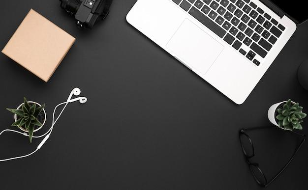 ノートパソコンとヘッドフォンを備えたワークステーションの平置き 無料写真
