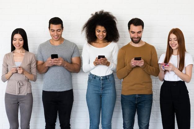 携帯電話でテキストメッセージを送る人々の正面図グループ 無料写真