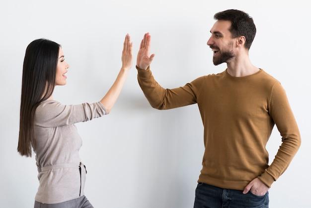 Счастливый молодой мужчина и женщина высокие пять вместе Бесплатные Фотографии