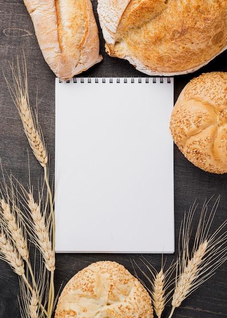 Пустой блокнот в окружении хлеба Бесплатные Фотографии