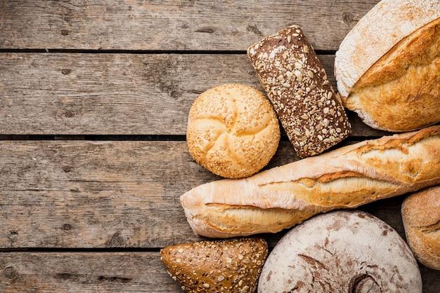 木製の背景を持つパンとパンのトップビュー 無料写真