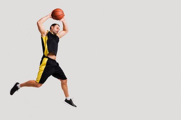 コピースペースでボールを投げながら空中でポーズのバスケットボール選手の側面図 無料写真