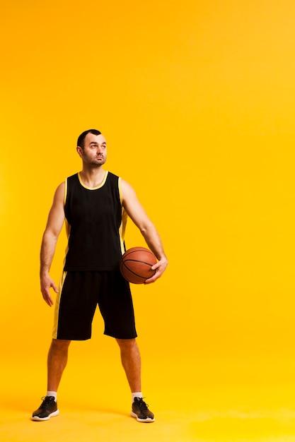 ヒップとコピースペースに近いボールでポーズのバスケットボール選手の正面図 無料写真
