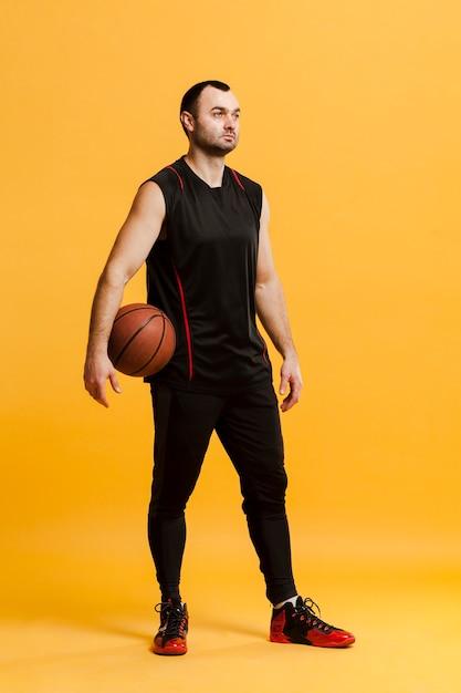 Вид спереди расслабленной мужской игрок позирует с баскетболом Бесплатные Фотографии