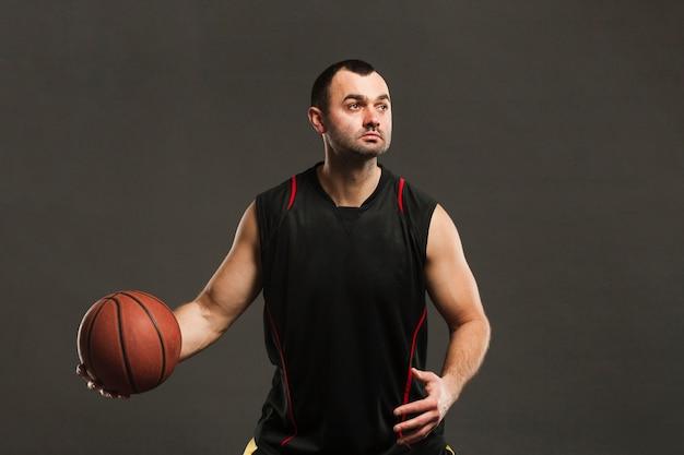 Вид спереди баскетболист позирует и играет с мячом Бесплатные Фотографии