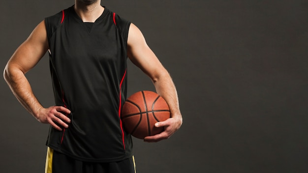 ポーズとボールを保持しているバスケットボール選手の正面図 無料写真