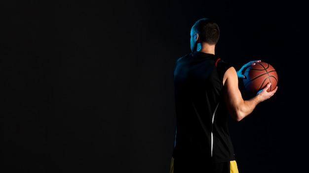 ボールとコピースペースを持つバスケットボール選手の背面図 無料写真