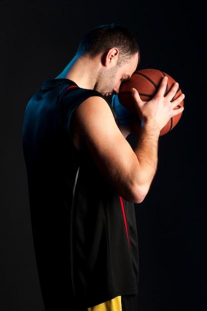 Вид сбоку баскетболиста, держащего мяч ко лбу Бесплатные Фотографии