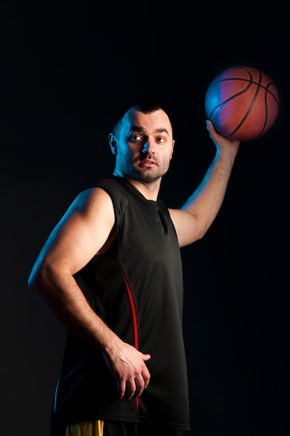 Вид сбоку баскетболиста с мячом в одной руке Бесплатные Фотографии