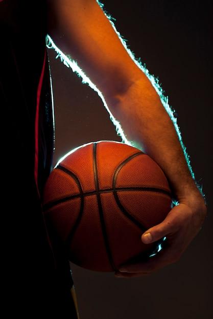 ボールを保持しているバスケットボール選手の正面図 無料写真