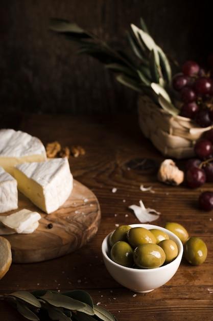 Высокий угол композиции оливок и сыра на столе Бесплатные Фотографии