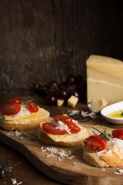 Высокий угол вкусный сыр с помидорами на столе Бесплатные Фотографии