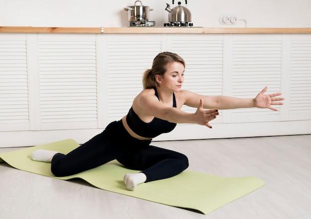 Женщина дома тренируется на коврике Бесплатные Фотографии