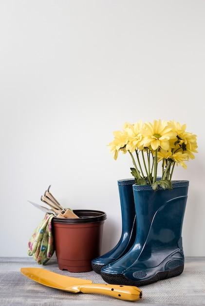 Вид спереди цветы в сапогах и садовые инструменты Бесплатные Фотографии
