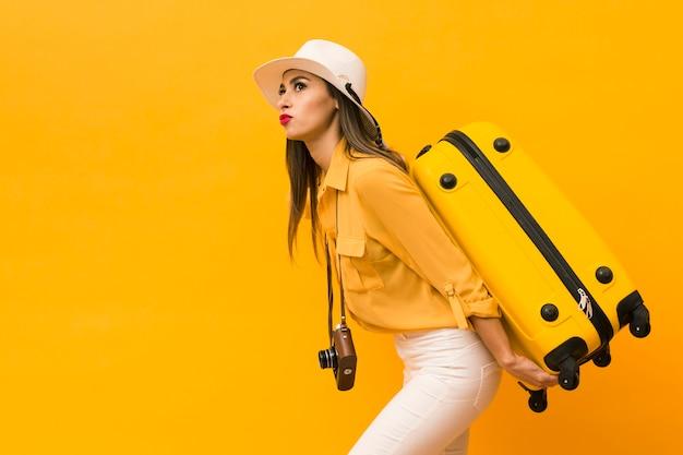 荷物とコピースペースを持つカメラを運ぶ女性の側面図 無料写真