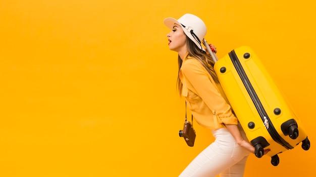 荷物とカメラを運ぶ女性の側面図 無料写真