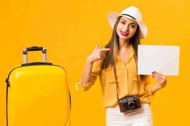 空白の紙を指差しながら荷物の横にポーズの女性の正面図 無料写真