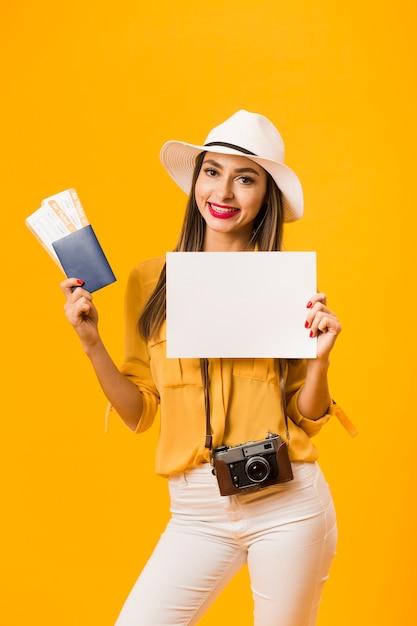 カメラを運ぶと飛行機のチケットとパスポートを保持している女性の正面図 無料写真