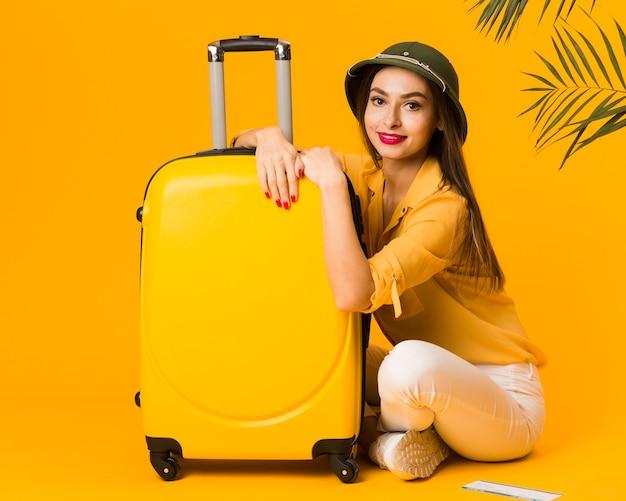 Вид сбоку женщины позируют рядом с ее багажом Бесплатные Фотографии