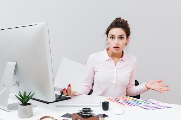Вид спереди женщины за столом, не подозревая, что только что произошло Бесплатные Фотографии