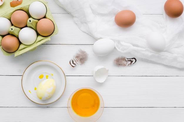Вид сверху на пасхальные яйца с красителем и перьями Бесплатные Фотографии