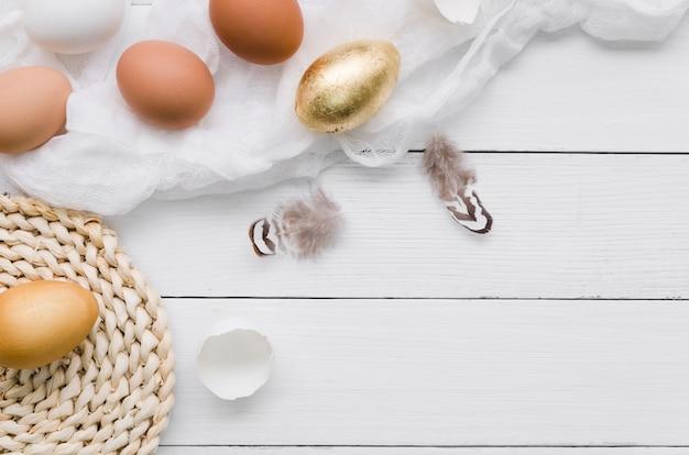Вид сверху пасхальных яиц с золотой краской и перьями Бесплатные Фотографии