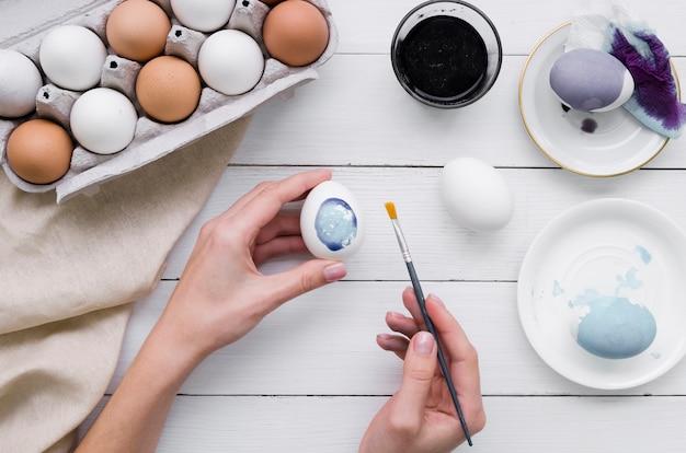 Взгляд сверху рук крася яичко на пасху с коробкой и краской Бесплатные Фотографии