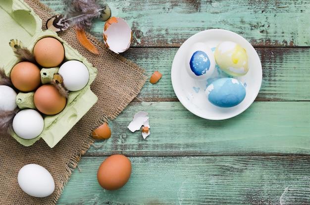 羽とイースターのプレートに塗られた卵のトップビュー 無料写真