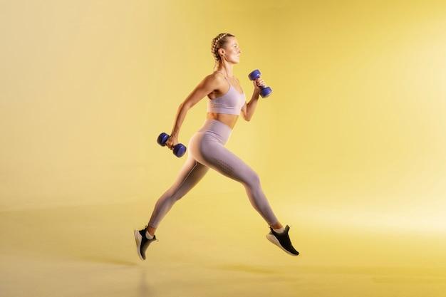 Тренировка молодой женщины с весами Бесплатные Фотографии