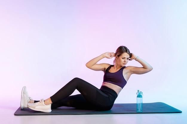 腹部運動をしているマットの上の女性 無料写真