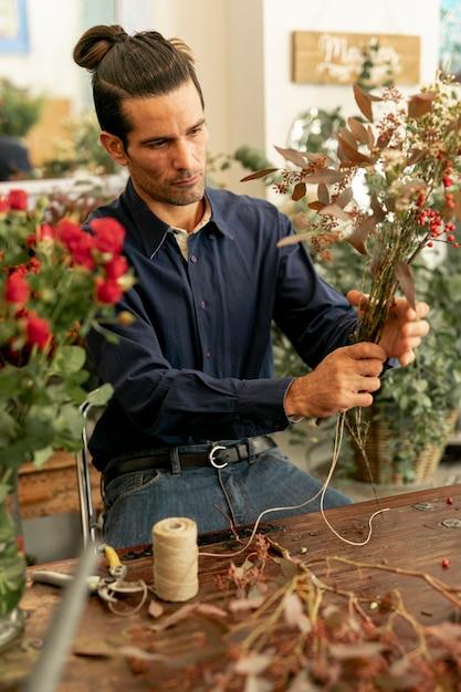Садовник мужчина с длинными волосами держит букет цветов Бесплатные Фотографии