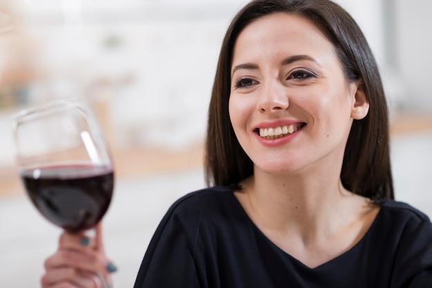 赤ワインのクローズアップのガラスを保持している美しい女性 無料写真
