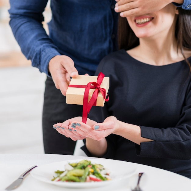 彼女に贈り物のクローズアップを与える前に彼のガールフレンドの目を覆っている男 無料写真