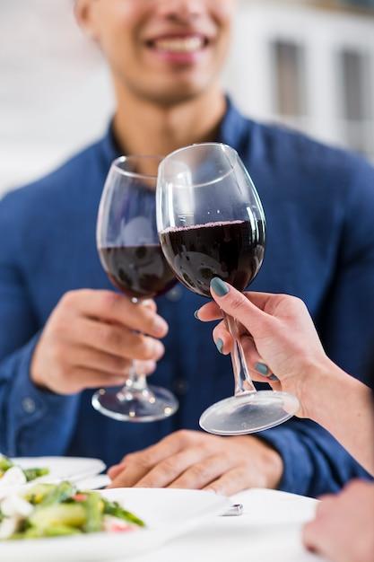 Пара, держащая бокалы с красным вином на день святого валентина Бесплатные Фотографии