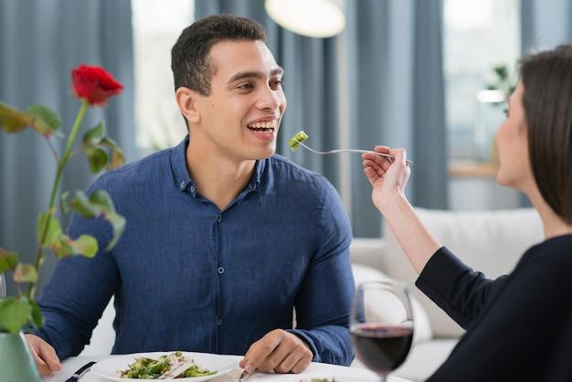 Женщина кормит мужа на романтическом ужине Бесплатные Фотографии