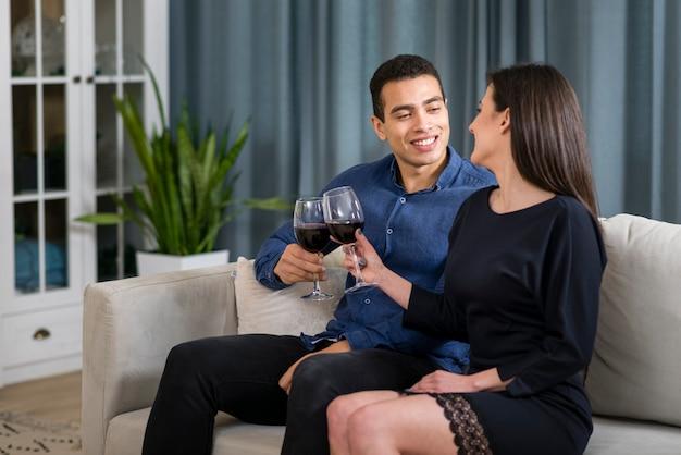 ソファに座ってワインを飲む男女 無料写真
