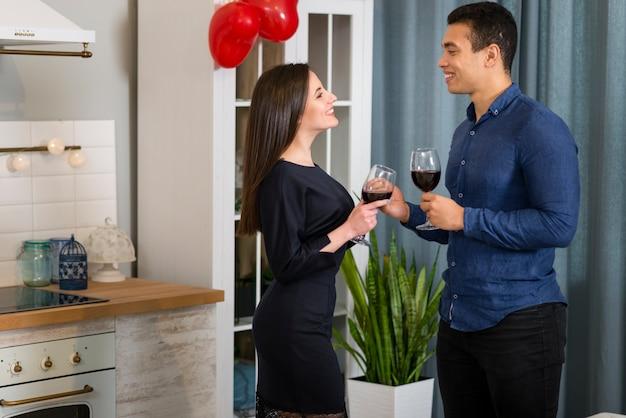 台所でワインのグラスを持っているカップル 無料写真