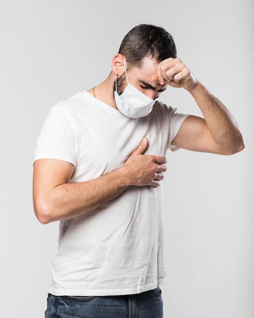 顔のマスクの咳を持つ成人男性の肖像画 無料写真