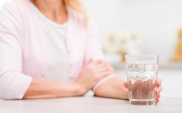 水のガラスを保持しているクローズアップの成熟した女性 無料写真