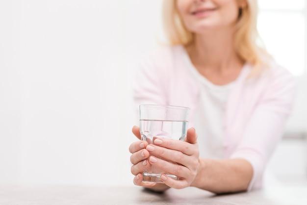 水のガラスを保持している美しい年配の女性 無料写真